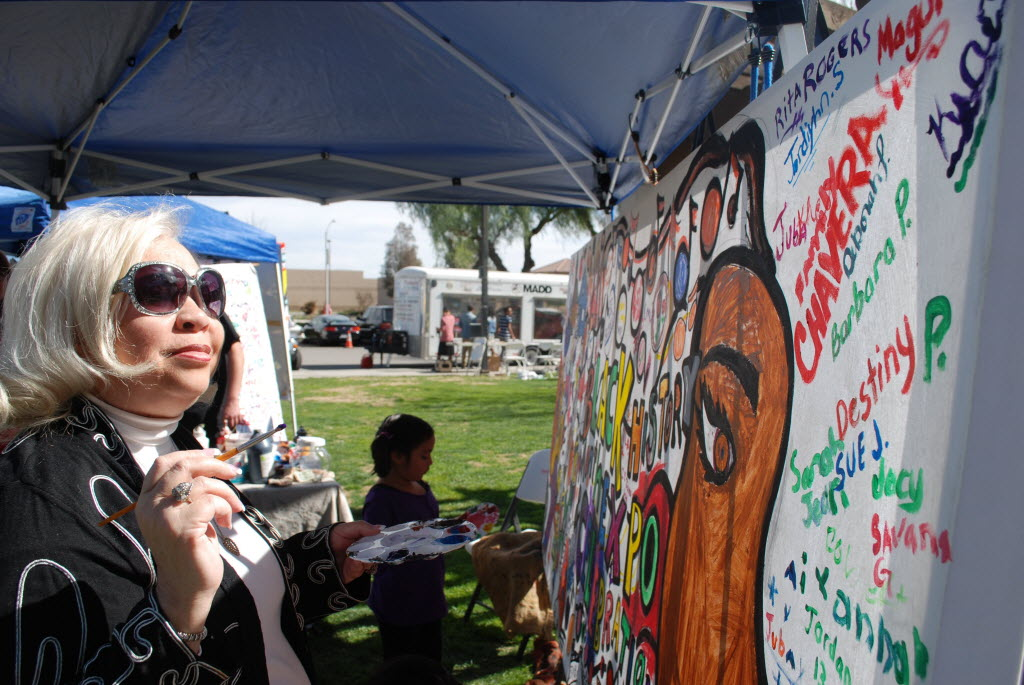934050 bytes; 3872 x 2592; Perris City Councilwoman Rita Rogers autographs a mural during the Black History Community Expo.