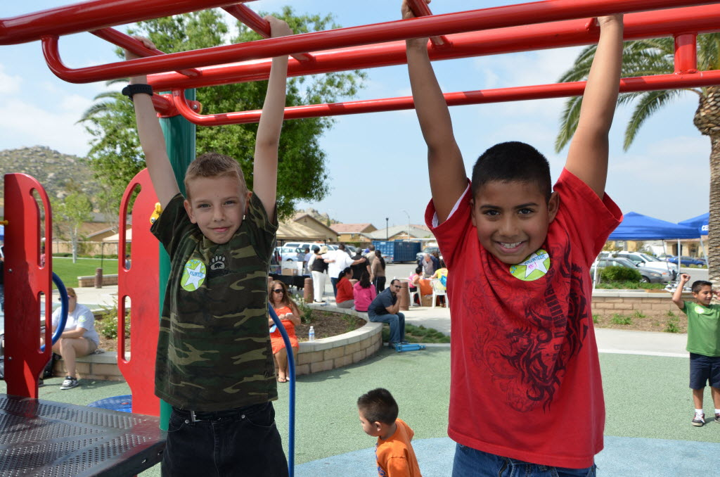 1246100 bytes; 4928 x 3264; May Ranch youngsters Noah Yazloff, 10, and Michel Flores, 8, hang on the monkey bars during the May