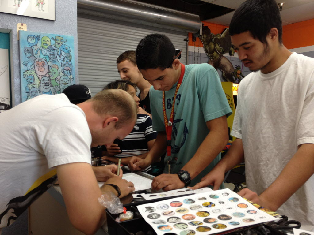 645652 bytes; 3264 x 2448; Zach Heinrichs, co-owner of Rocket Comics in Menifee, makes buttons for a crowd of customers on Free